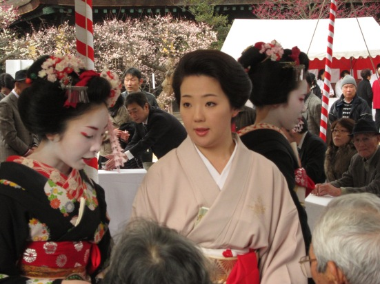 A mature geisha (centre) and two maiko, serving tea at the Plum Blossom Festival at Kitano Tenman-gū
