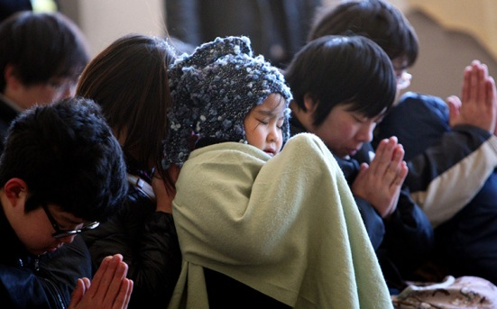 Children pray during a memorial ceremony in Kamaishi, Iwate prefecture