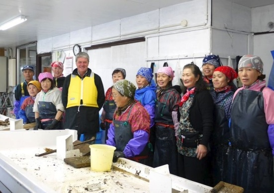 Workers at the rebuilt oyster processing plant pose with Yves Carcelle, Louis Vuitton's former Chairman and CEO, fifth from left. (Makiko Takahashi)