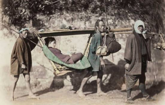 Group portrait of a woman in a kago, two bearers and a man using a carrying pole, Japan (Felice Beato, between 1863 and 1877)