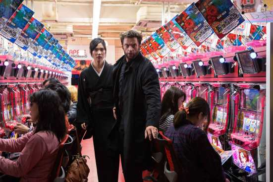 Logan (Hugh Jackman) and Mariko (Tao Okamoto) run through a pachinko parlour